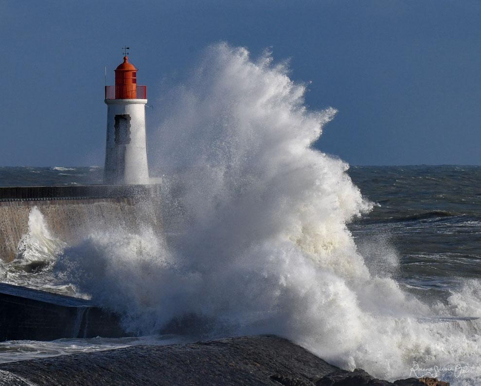 Vague se brisant pendants les tempêtes sur le phare rouge